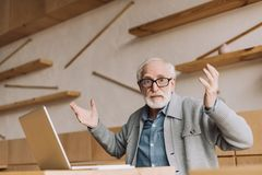 Bewildered senior man with laptop. Sitting in cafe and looking at camera with raised hands Royalty Free Stock Photography