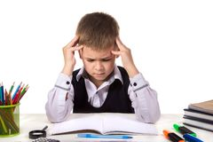 Bewildered thoughtful pupil sitting at the desk with hands over the head surrounded with stationery.  Royalty Free Stock Photo