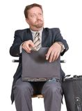 Bewildered travelling businessman. Travelling businessman or salesman with laptop and cell phone sitting bewildered after a phone call with a perplexed Royalty Free Stock Photos