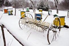 Bewirtschaften altes schneebedecktes Pferd gezeichneter Heurechen und Bienenstock im Winter Garten Stockfotografie