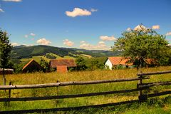 Bewirtschaften Sie auf einem Hügel eingezäunten Bretterzaun, der von den Klotz hergestellt wird Lizenzfreie Stockbilder