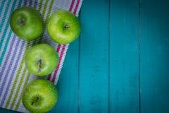 Bewirtschaften Sie frische organische grüne Äpfel auf hölzerner Retro- blauer Tabelle im Ba Lizenzfreie Stockfotos