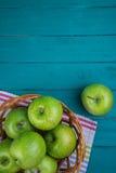 Bewirtschaften Sie frische organische grüne Äpfel im Korb auf hölzernem Retro- Blau Lizenzfreie Stockbilder