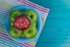 Bewirtschaften Sie frische organische grüne und rote Äpfel auf hölzernem Retro- blauem Vorsprung Stockfotos