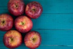 Bewirtschaften Sie frische organische rote Herbstäpfel auf hölzerner Retro- blauer Tabelle stockbild