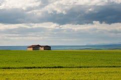 Bewirtschaften Sie Häuschen auf den Getreidegebieten mit dem blauen Himmel Wolken stockbild