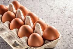 Bewirtschaften Sie rohes frisches Ei im Satz auf Spiegelei des grauen der Tabelle Omeletts der durcheinandergemischten Eier Stockfoto