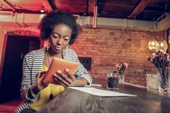 Bewitching lady clicking on tablet amid leaning on bar counter. Clicking on tablet. Bewitching glamorous vicennial focused Afro-American lady with lemon stock photo