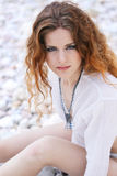 Bewitching sight. Red curly haired girl on the sea coast Royalty Free Stock Photos