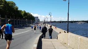Bewohner des Stadtwegs entlang den Ufergegend- und Marathonteilnehmern laufen gelassen auf der blockierten Straße der Stadt Große stock video footage