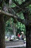 Bewohner entspannen sich im Park unter einer Statue Partini Balaikambang Stockbild