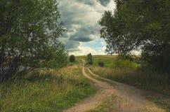 Bewolkt de zomerlandschap met grondlandweg royalty-vrije stock foto's