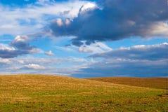 Bewolkt hemel en gebied na oogst Stock Foto's