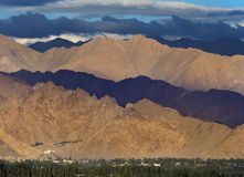 Bewolkt weer in de bergen: de blauwe onweerswolken gegoten schaduwen op de series, worden een deel van de heuvels aangestoken doo Stock Afbeeldingen