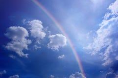 Bewolkte blauwe hemel met magische regenboog en licht stock foto's