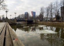 Bewolkte de winterdag op een rivier met drijvende ijsijsschollen die high-rise gebouwen en Uitwisselingsbrug in het centrale deel royalty-vrije stock foto's