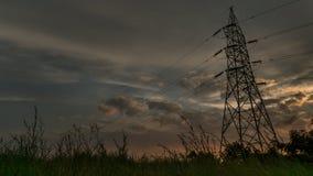 Bewolkte die zonsondergang met toren in voorgrond wordt gevangen stock afbeeldingen