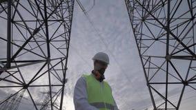 Bewolkte hemel en een mannelijke technicus die tussen lange ETL-torens werken stock video