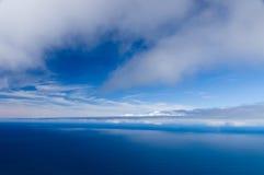 Bewolkte hemel en kalme oceaanachtergrond Stock Afbeeldingen