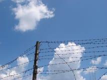 Bewolkte hemel met ruwe draadomheining 1 Stock Afbeeldingen