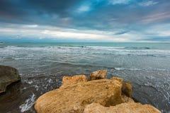 Bewolkte hemel over overzees, grote rots op kust Royalty-vrije Stock Foto
