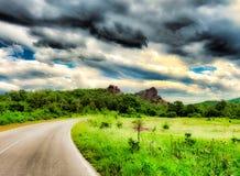 Bewolkte Hemel over Rocky Hill onder Groene Bos, Weide, en Weg Royalty-vrije Stock Afbeeldingen