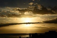 Bewolkte Strandzonsondergang - met een mens status Stock Fotografie