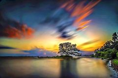 Bewolkte zonsondergang en een rotsachtig strand met een lange blootstelling Stock Foto's