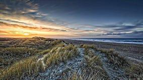 Bewolkte zonsondergang en een zandig strand Stock Afbeeldingen