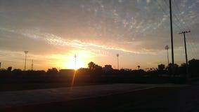 bewolkte zonsondergang met zon Stock Afbeeldingen