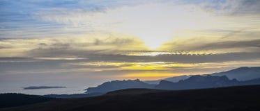 Bewolkte zonsondergang over bergen Stock Afbeelding