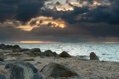 Bewolkte zonsondergang over een meer met regenachtige donkere onweerswolken en sunbe stock foto
