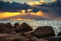 Bewolkte zonsondergang over een meer met regenachtige donkere onweerswolken en zonnestralen en zonharpen stock fotografie