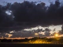 Bewolkte zonsondergang over zandduinen stock foto's