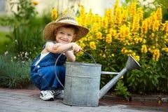 Bewässerungsblumen des kleinen Jungen Stockbild