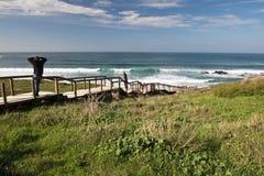 Bewundern wunderbarer Meerblick und Surfer der Leute auf dem Überraschen von Atlantik setzen amado auf den Strand Stockfotografie