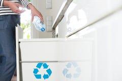 Bewusste Hausfrau, die Plastikflaschen trennt lizenzfreie stockfotografie