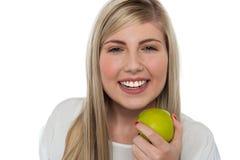 Bewusstes Mädchen der Gesundheit, das grünen Apfel anhält Stockfotos