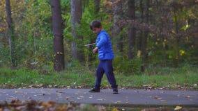 Beyblade del giroscopio del juguete de los niños al aire libre en parque del otoño