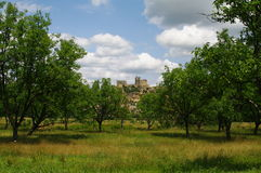 Beynac castel. At the end of orchard against the clouds and blue sky in dordogne,in france Stock Photography