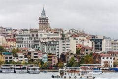 The Beyoglu tower. Istanbul, Turkey-10th October 2011: The Beyoglu tower rises above other buildings with the Bosphorous below stock photos