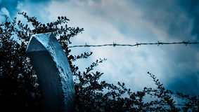 Beyond the barbed wire. Melancholy twilight. Sad view of blue sky in moonlight through the spiked fence. Dramatic scene. Dark gloomy background stock image