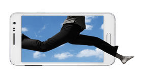 Beyond Borders. Bottom portion of human body jumping from within the smart phone screen outside. Front feet extending beyond the phone. Isolated on white Stock Photos