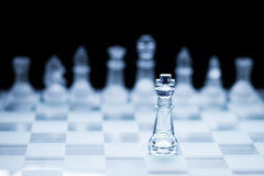 Beyond the dark curtain. Photo of chess king standing in front of the other colour set in bright background Royalty Free Stock Image