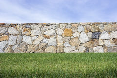 Beyond the fence. Stone fence between lawn and clear sky Stock Photography