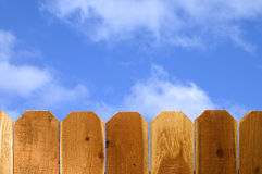 Beyond the fence. Redwood fence with blue sky and puffy clouds royalty free stock photography