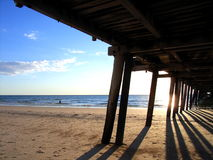 Beyond the Henley Jetty 1. Photo taken of the sun setting from underneath the jetty at Henley Square (Adelaide, Australia), including a man swimming in the ocean royalty free stock photography