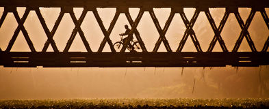 Beyond The Obstacle. A boy riding bicycle in a misty morning Royalty Free Stock Images