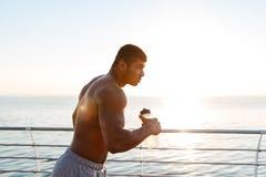 Bez koszuli afrykański sportowiec z butelką wodny bieg na molu Zdjęcie Royalty Free