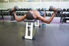 Bez koszuli mężczyzna ćwiczy z dumbbells w gym Zdjęcia Royalty Free